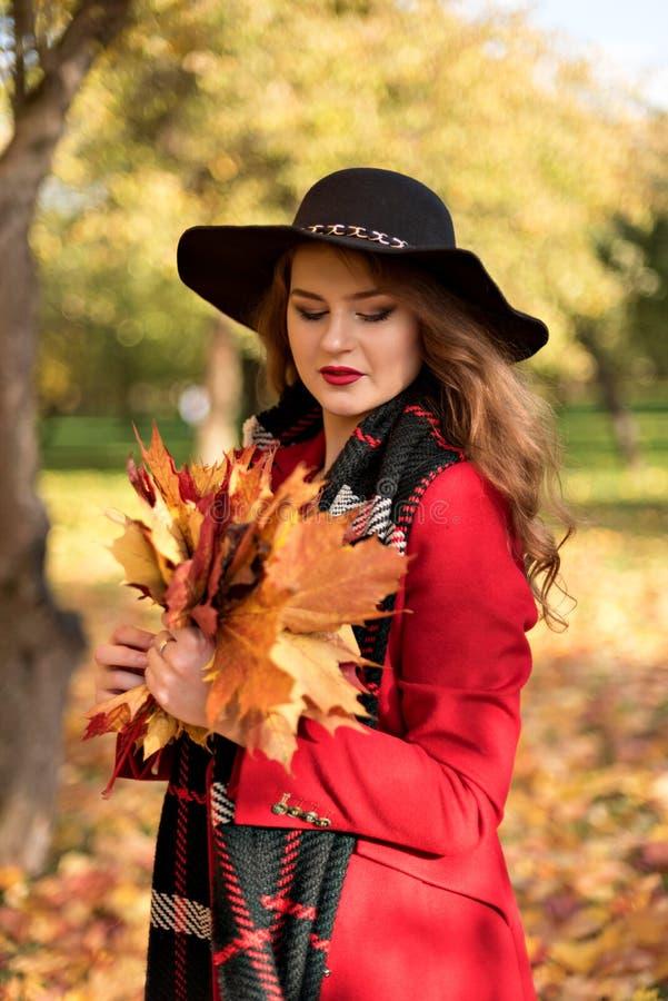 Het portret van een meisje met ogen sloot met een boeket van gele de herfstbladeren in een rode laag en een zwarte hoed stock fotografie