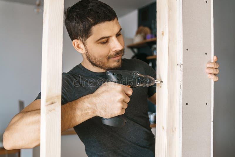 Het portret van een mens in huiskleren met een schroevedraaier in zijn hand bevestigt een houtconstructie voor een venster in zij stock foto's