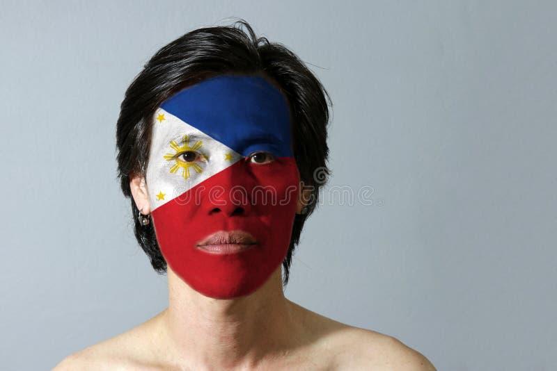 Het portret van een mens met de vlag van de Filippijnen schilderde op zijn gezicht op zwarte achtergrond stock foto