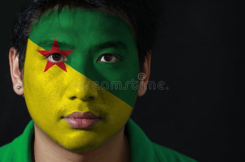 Het portret van een mens met de vlag van Frans-Guyana schilderde op zijn gezicht op zwarte achtergrond royalty-vrije stock afbeeldingen