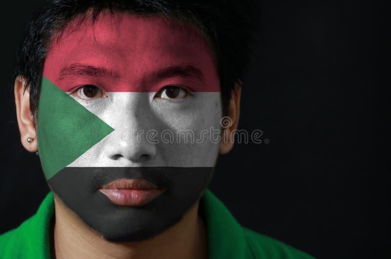 Het portret van een mens met de vlag van de Soedan schilderde op zijn gezicht op zwarte achtergrond royalty-vrije stock foto's