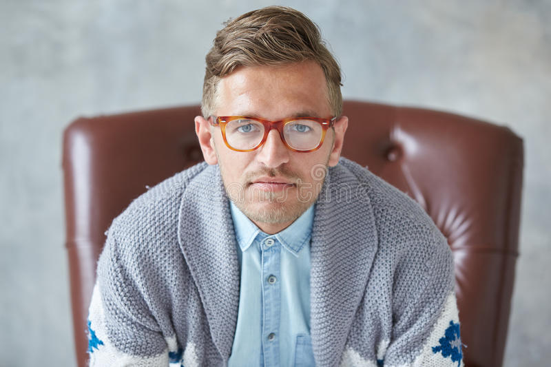 Het portret van een modieuze intelligente mens met glazen staart in de camera, goede mening, klein ongeschoren, charismatisch, bl stock fotografie