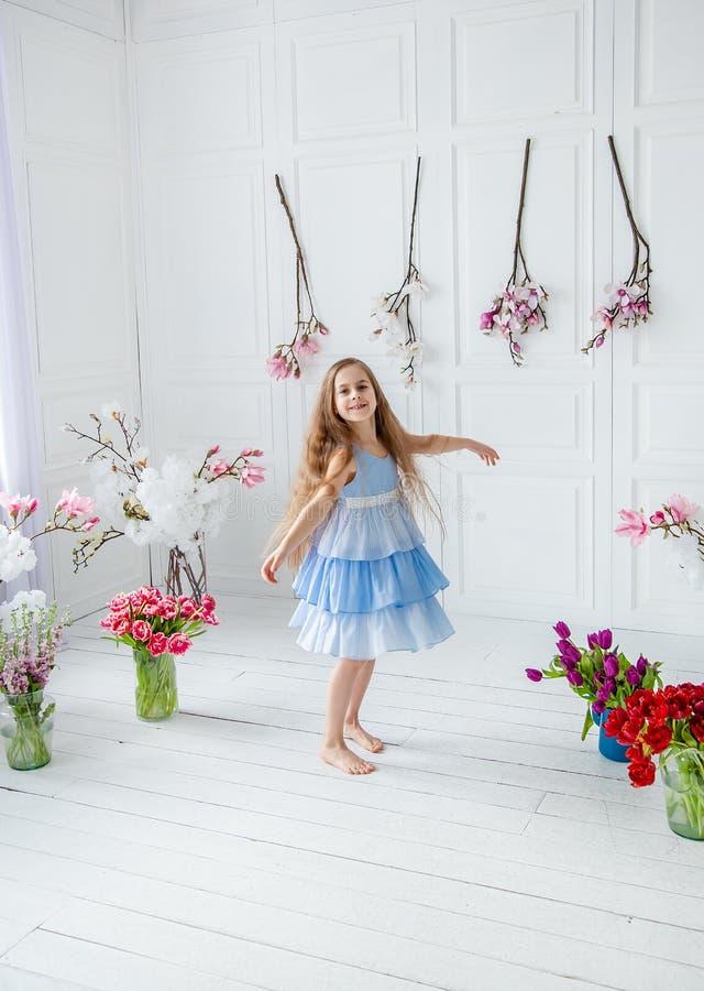 Het portret van een mooi blauw-eyed meisje, een klein meisje onder de lente bloeit in een heldere ruimte royalty-vrije stock foto's