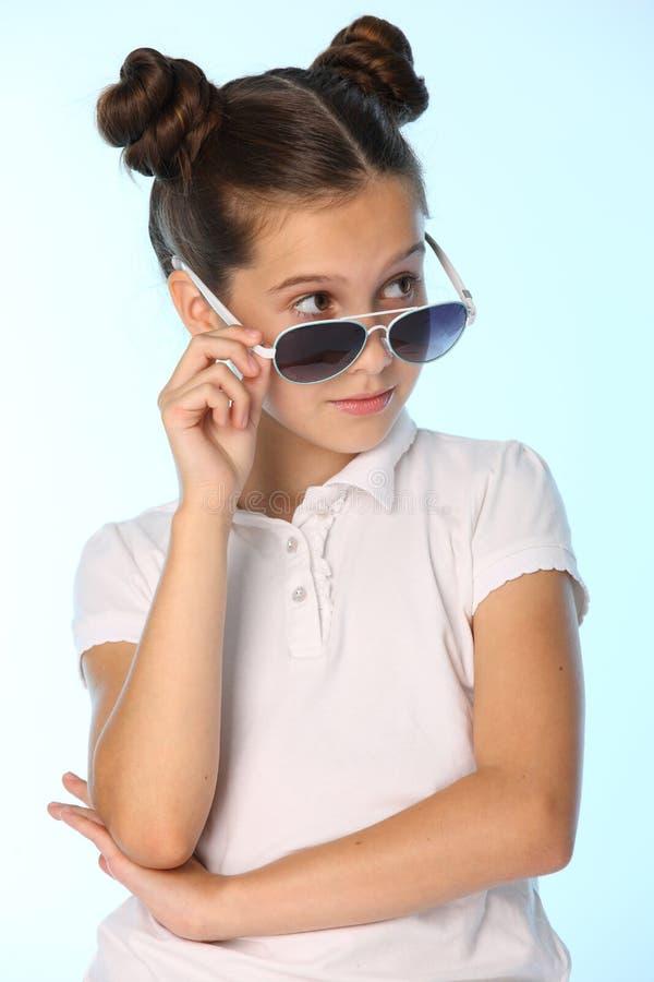 Het portret van een mooi donkerbruin kindmeisje kijkt koel met zonnebril, weg kijkt zij stock afbeelding