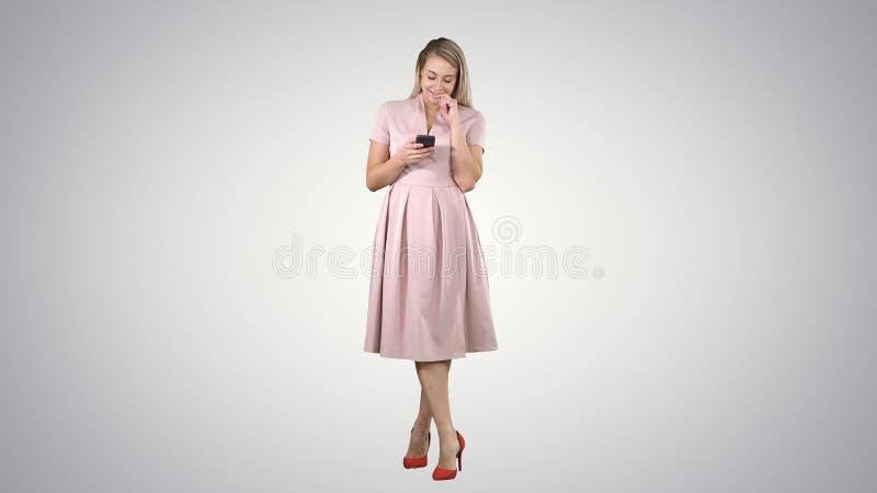 Het portret van een mooi glimlachend meisje in de zomer kleedt het gebruiken van mobiele telefoon, die bericht op gradiëntachterg royalty-vrije stock foto's