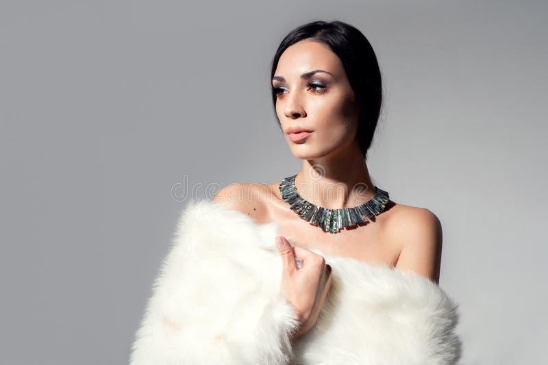Het portret van een mooi jong Kaukasisch meisje met naakte schouders en mooie avondsamenstelling kleedde zich in kunstmatig wit b royalty-vrije stock foto's