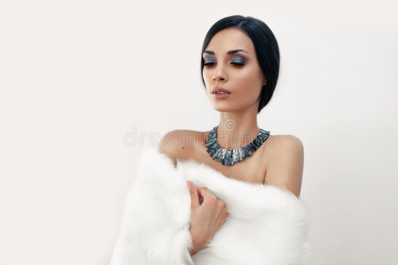Het portret van een mooi jong Kaukasisch meisje met naakte schouders en mooie avondsamenstelling kleedde zich in kunstmatig wit b stock fotografie