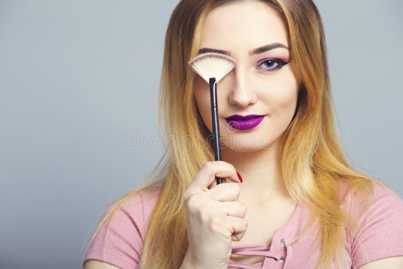 Het portret van een mooi jong meisje in een studio, vrouw behandelt het oog met make-upborstel, schoonheidsmiddelen en natuurlijk royalty-vrije stock afbeelding