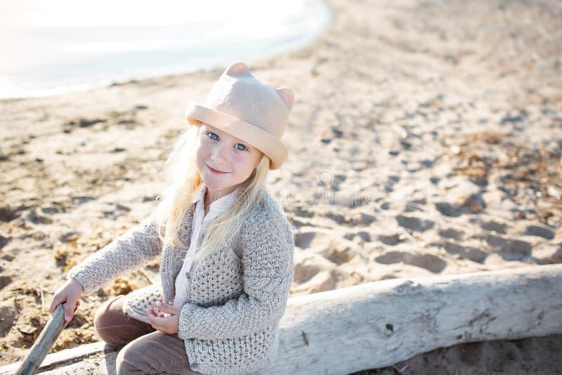 Het portret van een mooi meisje weet een lichte hoed en een gebreid jasje op een strand stock afbeeldingen
