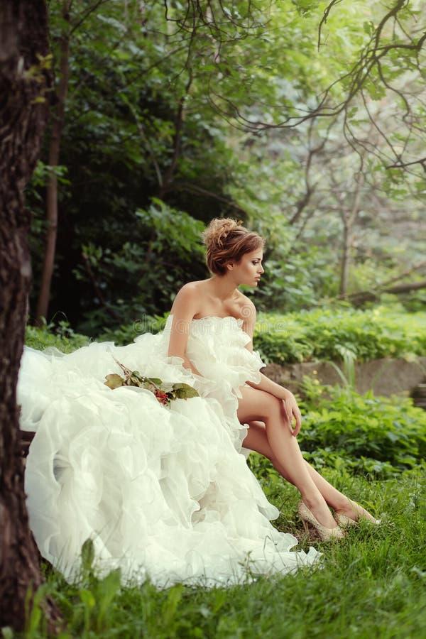 Het portret van een mooie bruidvrouw zit in een profiel en onderzoekt de afstand royalty-vrije stock afbeeldingen