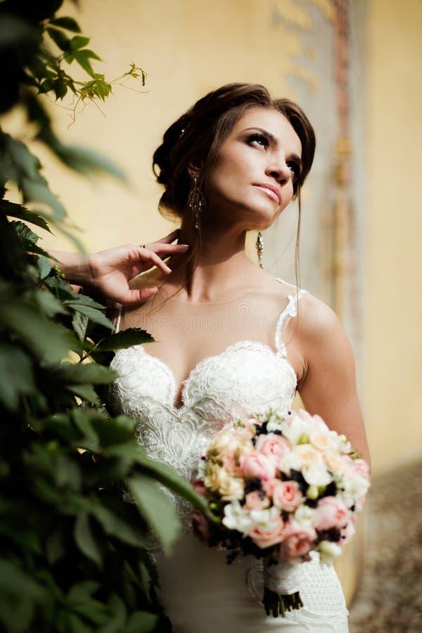 Het portret van een mooie gelukkige donkerbruine bruid in holding van de huwelijks de witte kleding dient boeket in openlucht van stock foto