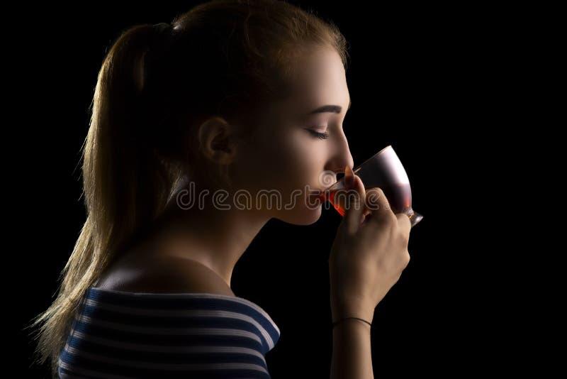 het portret van een mooie gir het drinken thee, het gezicht van de vrouw met ogen sloot op een zwarte achtergrond royalty-vrije stock afbeelding