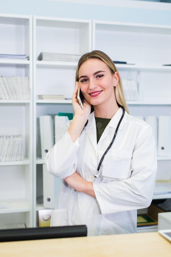 Het portret van een mooie glimlachende verpleegster bij bureaupost terwijl het spreken op de telefoon en voltooit een medische in royalty-vrije stock afbeelding