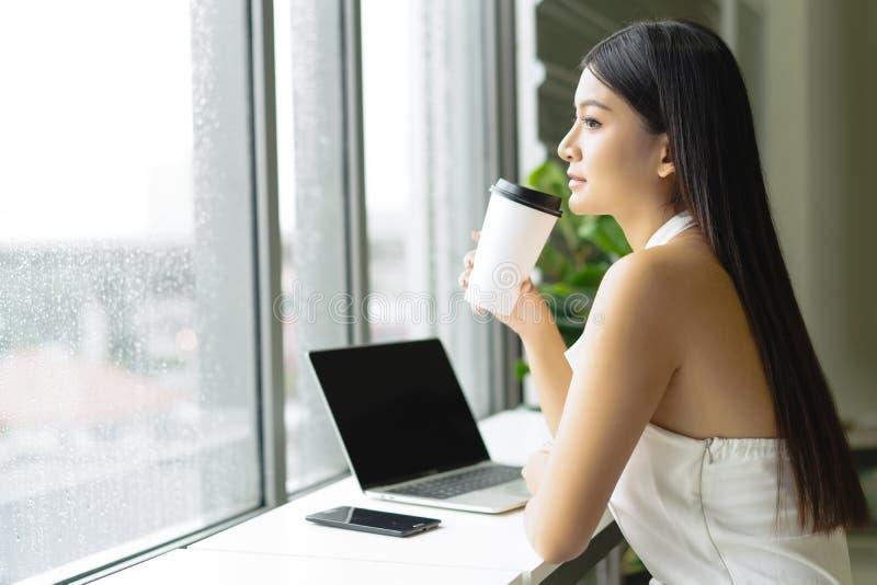 Het portret van een mooie jonge Aziatische vrouwenzitting in de koffiemok van de cafetariaholding terwijl het kijken weg op lijst stock foto's
