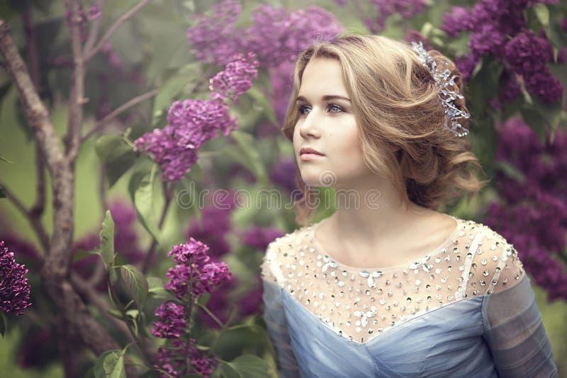 Het portret van een mooie jonge blonde vrouw in lilac struiken, het bewonderen bloeit stock foto