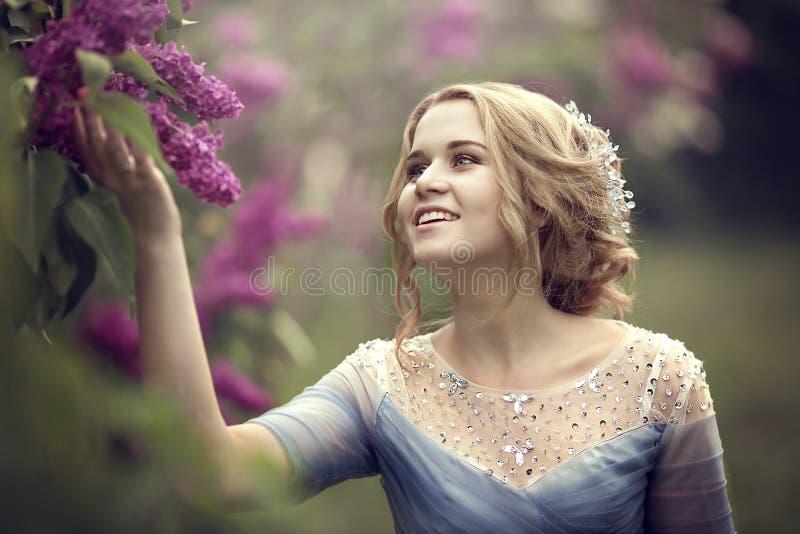 Het portret van een mooie jonge blonde vrouw in lilac struiken, het bewonderen bloeit stock afbeeldingen