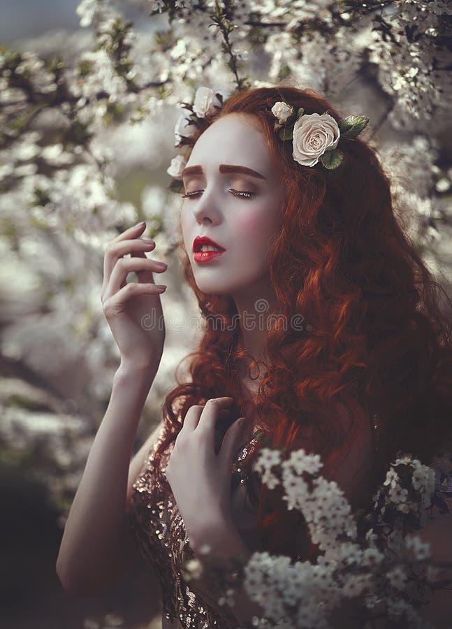 Het portret van een mooie jonge sensuele vrouw met zeer lang rood krullend haar in de lente bloeit Kleuren van de Lente stock foto's