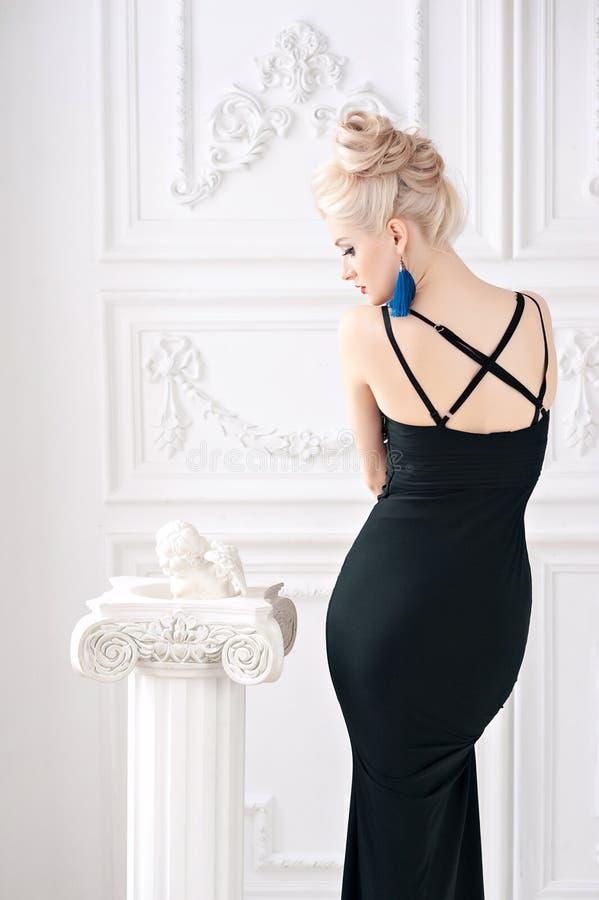 Het portret van een mooie jonge sexy blonde vrouw met zachte make-up in stiekeme zwarte kleding handhaafde goed lichaam en gezich royalty-vrije stock foto