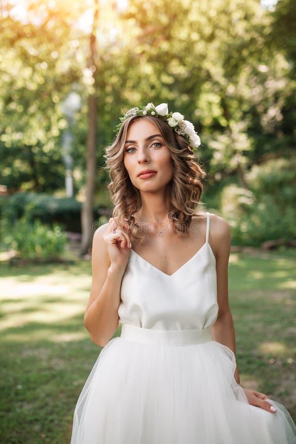 Het portret van een mooie jonge sexy meisjesbruid met bloemen in haar haar kijkt aantrekkelijk in een witte kleding royalty-vrije stock foto