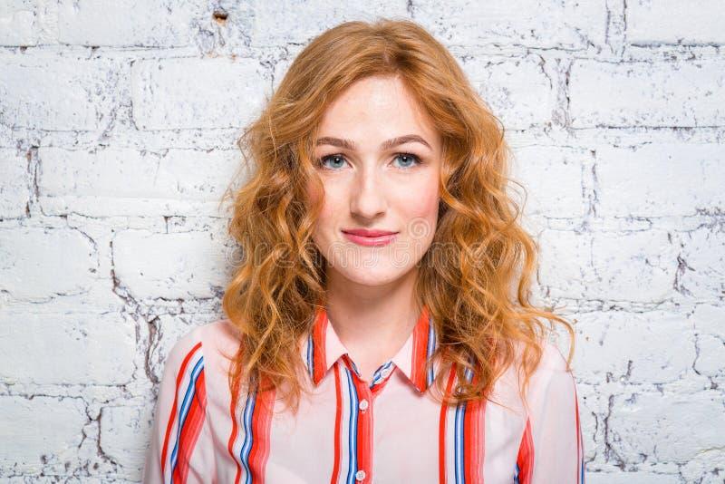 Het portret van een mooie mooie jonge studente met rode krullende haar en sproeten op haar gezicht leunt tegen een bakstenen muur royalty-vrije stock foto