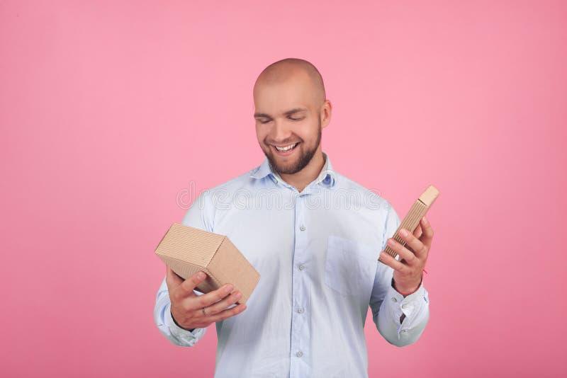 Het portret van een mooie kale mens met een baard kleedde zich in een wit overhemd opent een gift met blije emoties tribunes voor stock foto's