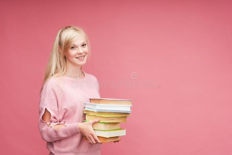 Het portret van een mooie studente met een rugzak en een stapel boeken in zijn handen glimlacht bij de roze achtergrond stock foto's