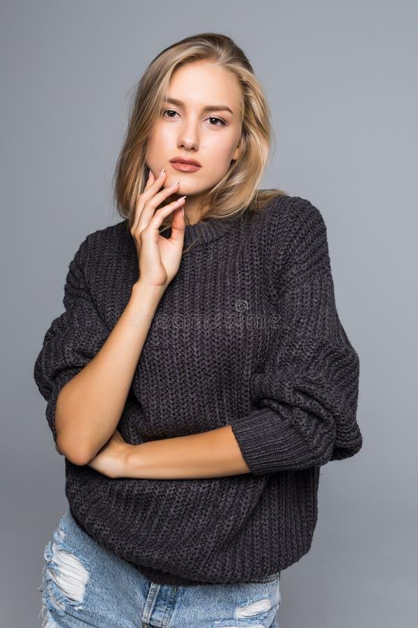 Het portret van een Mooie Vrouw die Warm dragen breit Sweater op een grijze geïsoleerde achtergrond stock afbeeldingen