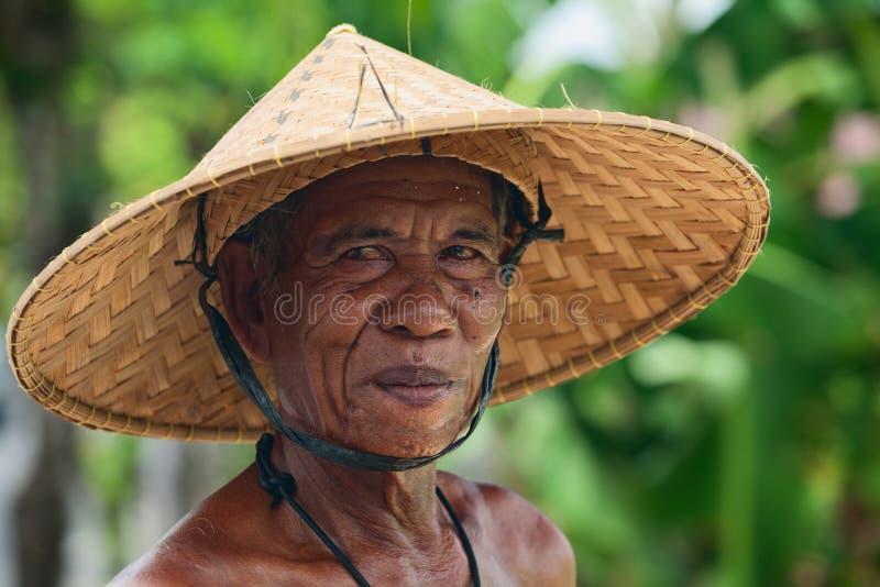 Het portret van een niet geïdentificeerde oude Balinese landbouwer met een gerimpeld gezicht in traditioneel stro breed-brimmed h stock fotografie