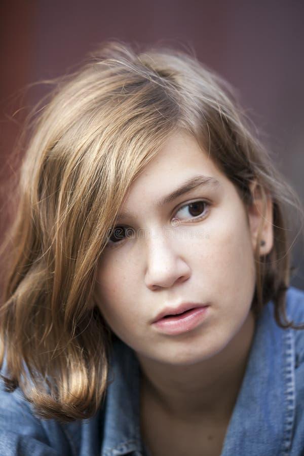 Het portret van een peinzend jong meisje met een kapsel royalty-vrije stock afbeelding