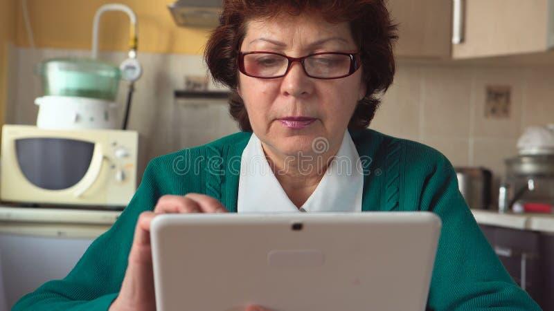 Het portret van een rijpe vrouw met glazen gebruikt thuis een Tabletpc stock foto