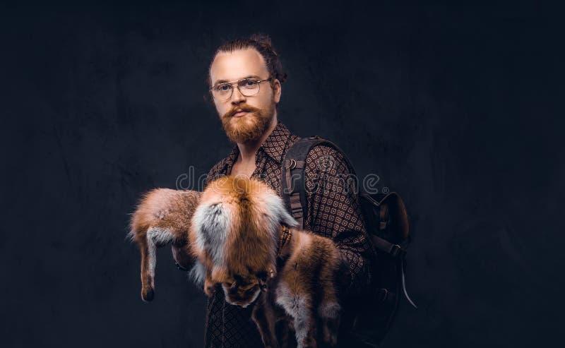 Het portret van een roodharige hipster kerel in glazen gekleed in een bruin overhemd, houdt de voshuid, die bij een studio stelle stock foto's