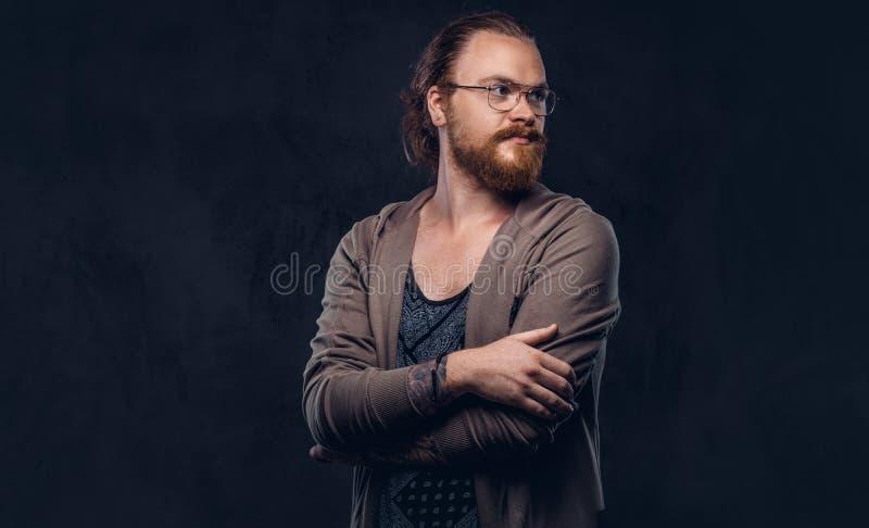 Het portret van een roodharige hipster mannetje kleedde zich in vrijetijdskleding met glazen en volledige baard, die zich met gek royalty-vrije stock foto's