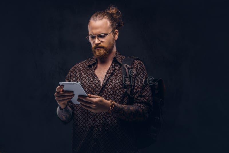 Het portret van een roodharige hipster student in glazen gekleed in een bruin overhemd, houdt een rugzak en een digitale tablet,  stock afbeelding