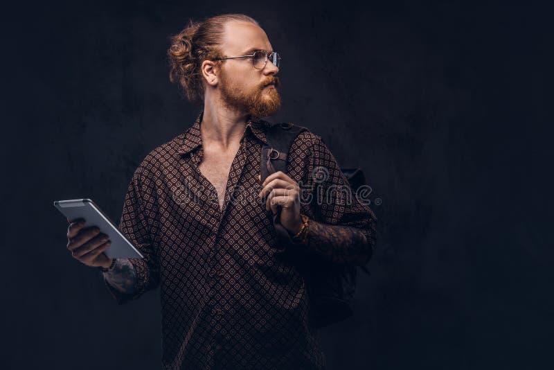 Het portret van een roodharige hipster student in glazen gekleed in een bruin overhemd, houdt een rugzak en een digitale tablet,  stock fotografie