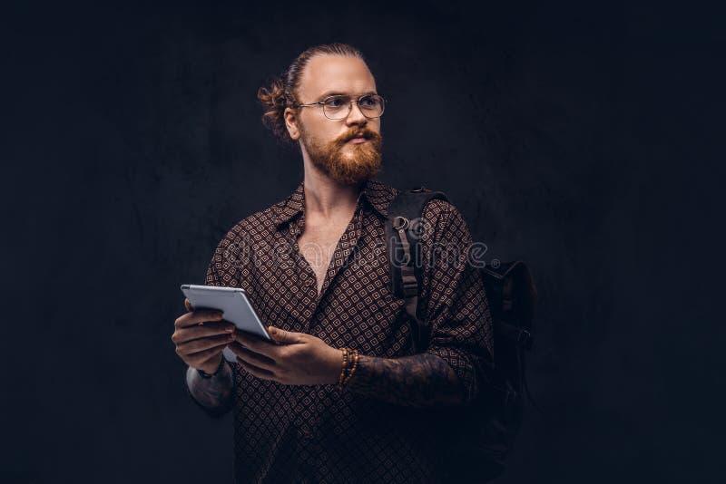 Het portret van een roodharige hipster student in glazen gekleed in een bruin overhemd, houdt een rugzak en een digitale tablet,  royalty-vrije stock afbeeldingen