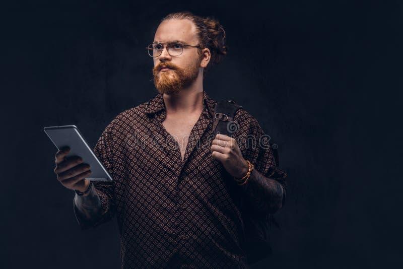 Het portret van een roodharige hipster student in glazen gekleed in een bruin overhemd, houdt een rugzak en een digitale tablet,  stock foto's