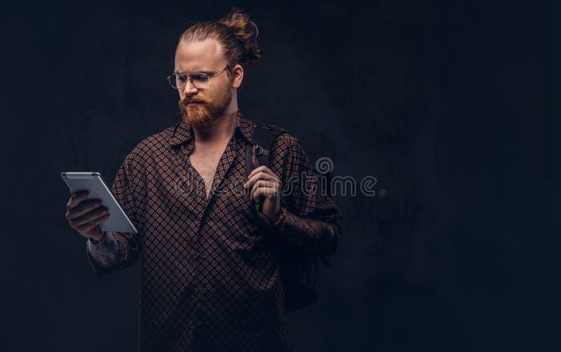 Het portret van een roodharige hipster student in glazen gekleed in een bruin overhemd, houdt een rugzak en een digitale tablet,  stock afbeeldingen