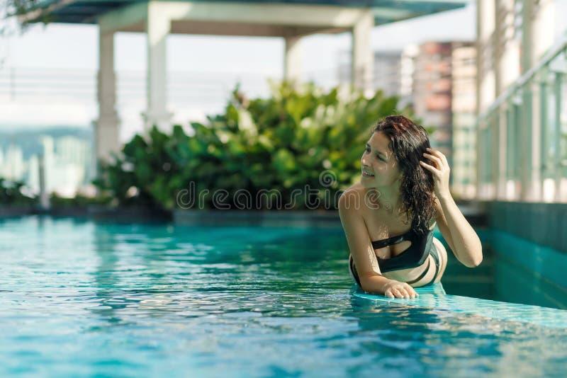 Het portret van een sexy glimlachende Kaukasische vrouw in een zwempak legt op de rand van een dakpool met groene struiken en sta royalty-vrije stock foto