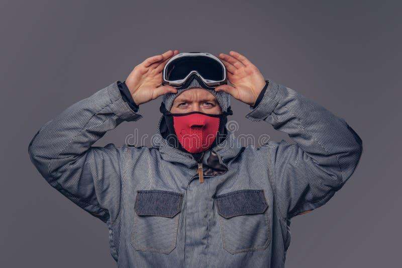 Het portret van een snowboarder gekleed in een volledig beschermend toestel voor extream het snowboarding zet op glazen terwijl s royalty-vrije stock foto