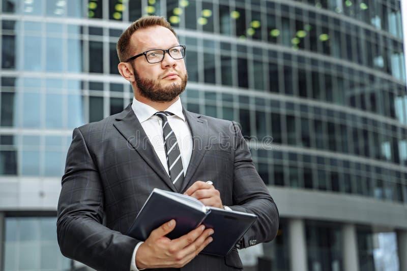 Het portret van een succesvolle bedrijfsmens in een kostuum en de glazen met een notitieboekje in zijn handen op de achtergrond v stock foto