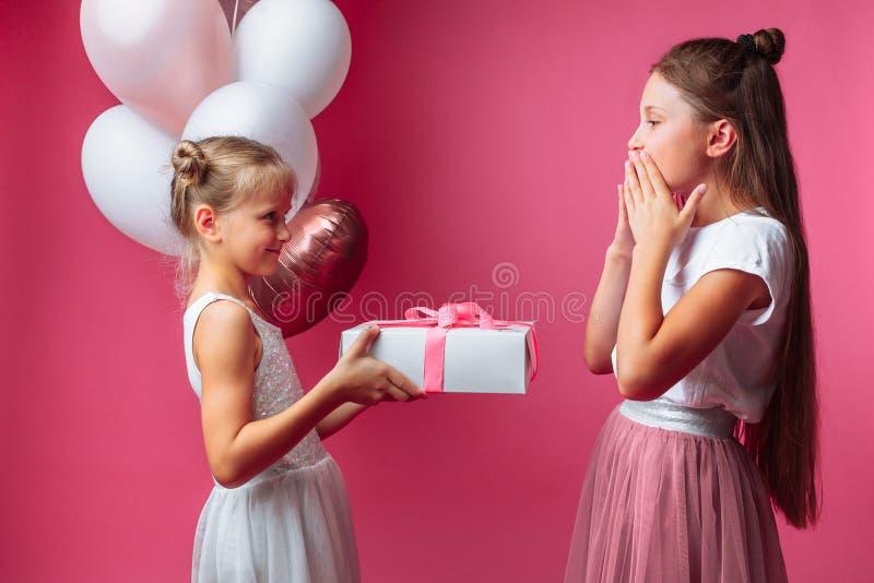 Het portret van een tiener op een roze achtergrond, met giften, verjaardagsconcept, één geeft een ander meisje een gift stock foto