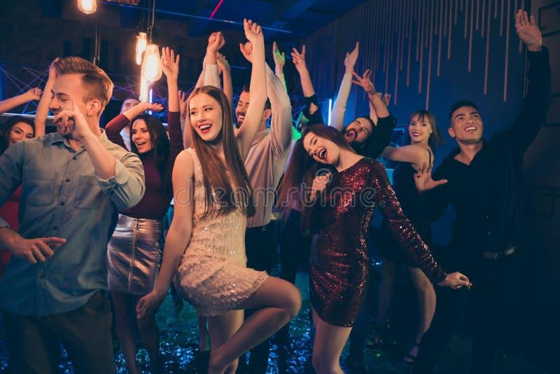 Het portret van een vrolijke groep mensen die mates dansen in een nachtclub heeft plezier op noel discotheque slijt een rok met e stock fotografie