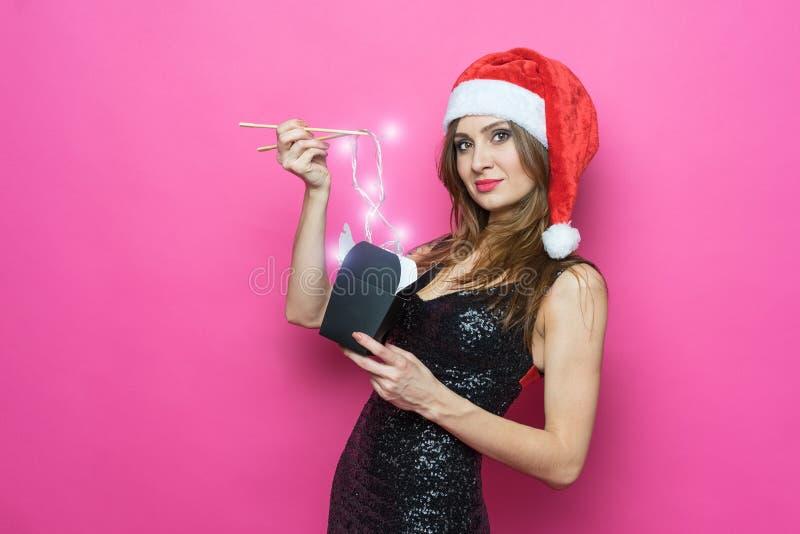 Het portret van een vrolijke lachende donkerbruine vrouw in Kerstmishoed en uitstekende zwarte kleding houdt in haar hand een doc stock fotografie