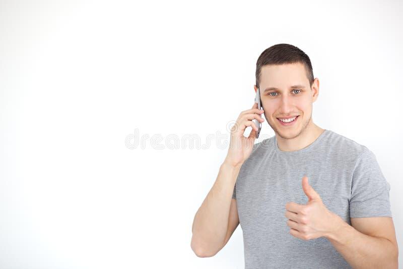 Het portret van een vrolijke, positieve, aantrekkelijke kerel met varkenshaar in een grijze T-shirt, met een zwarte het schermsma stock afbeelding