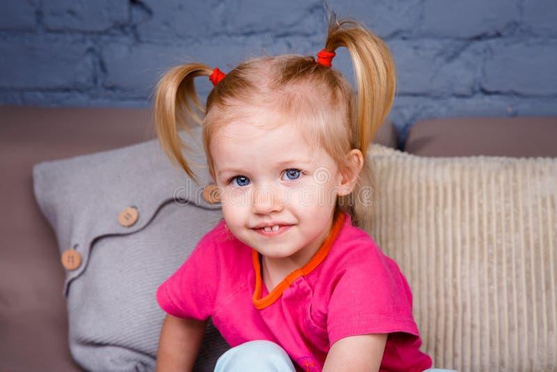 Het portret van een weinig grappig blondemeisje met blauwe ogen en een grappig kapsel ploetert en speelt thuis op de bank Hij lac royalty-vrije stock foto