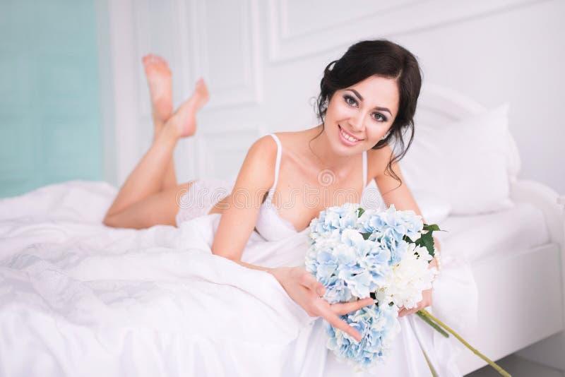 Het portret van elegante vrouw met krullend haar met bloemen ligt in bed stock afbeelding