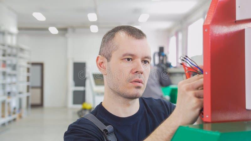 Het portret van elektricien op overall werkt met energiepaneel en machinesmateriaal aan installatie royalty-vrije stock afbeeldingen