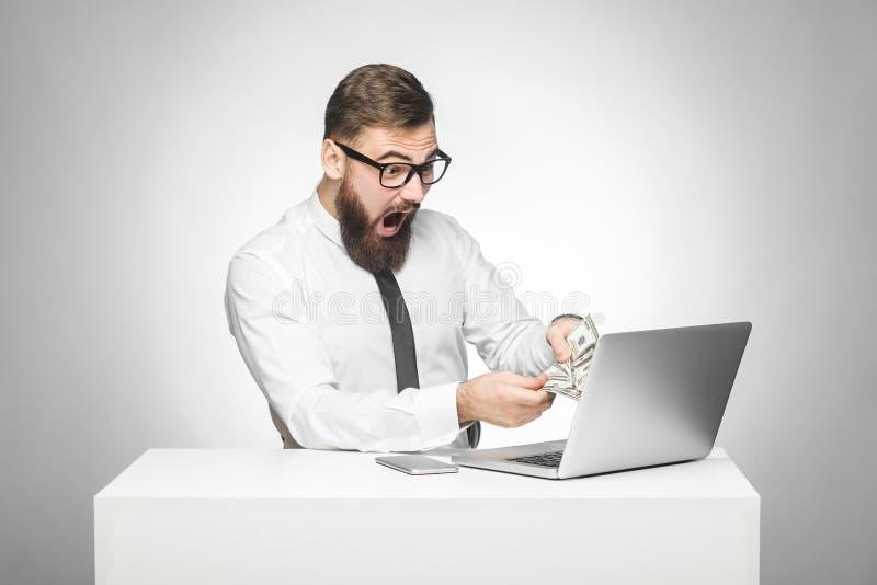 Het portret van emotionele geschokte jonge zakenman in wit overhemd en de avondkleding zitten in het contante geld van de bureauh stock afbeelding