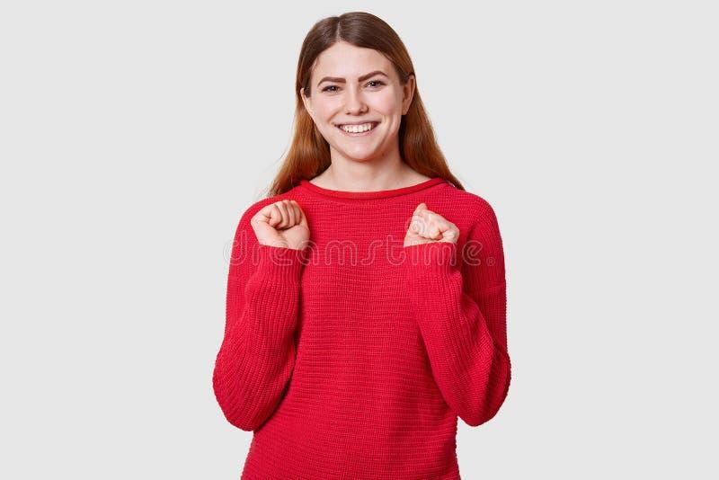 Het portret van energieke vrouw heeft bruin recht haar, dichtklemt vuisten met geluk, heeft toothy glimlach, geklede toevallige r stock fotografie