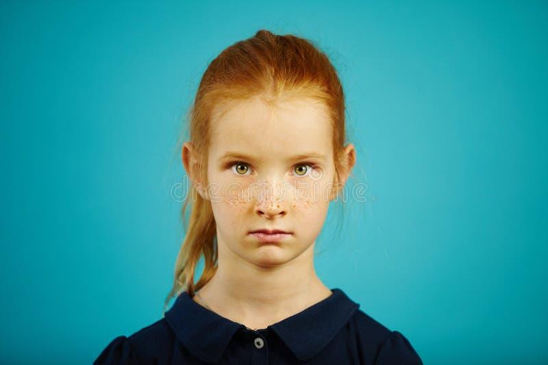 Het portret van ernstig zeven éénjarigenmeisje met sproeten en rood haar op blauw geïsoleerde achtergrond, drukt eerlijkheid uit  stock afbeelding